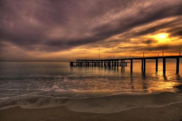 Sonnenuntergang am strand neben dem pier Kostenlose Fotos