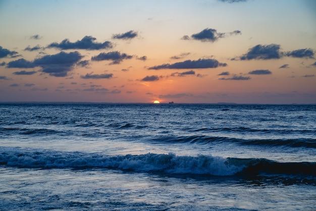 Sonnenuntergang, blaues meer, hintergrundboot, orange himmel mit wolken, são luis-stadt, maranhão-staat Premium Fotos