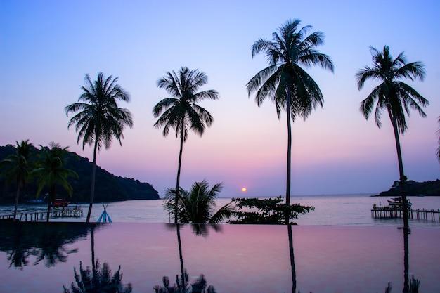 Sonnenuntergang, der über den wasseroberflächenvordergrund mit kokosnussbaumbereich ao knall bao nachdenkt Premium Fotos