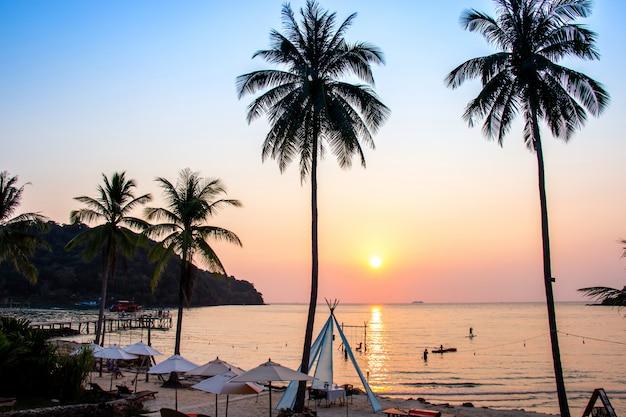 Sonnenuntergang, der über den wasseroberflächenvordergrund mit kokosnussbaumbereich ao-knallbao bei koh kood nachdenkt. Premium Fotos