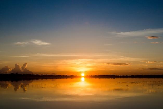 Sonnenuntergang im see. schöner sonnenuntergang hinter den wolken über dem überseelandschaftshintergrund. Premium Fotos