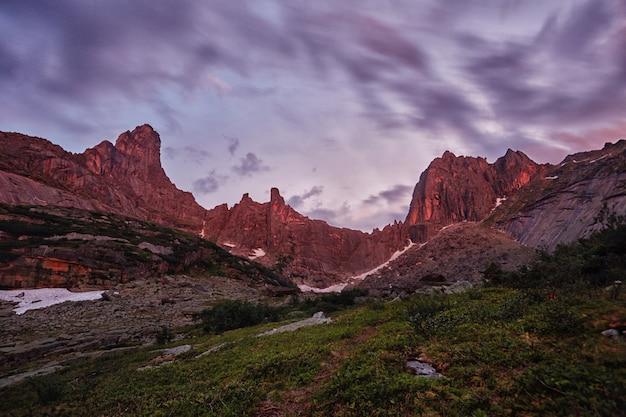 Sonnenuntergang in den bergen nahe see, sonnenlicht reflektiert Premium Fotos
