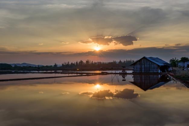 Sonnenuntergang und wasser nahe altem haus, sonnenuntergang Premium Fotos