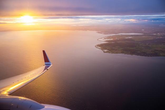 Sonnenunterganghimmel auf flugzeugfenster über kopenhagen, dänemark im freitagabendflug Premium Fotos