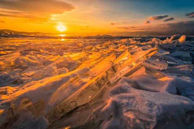 Sonnenunterganghimmel mit natürlichem brechendem eis über gefrorenem wasser auf dem baikalsee, sibirien, russland. Premium Fotos