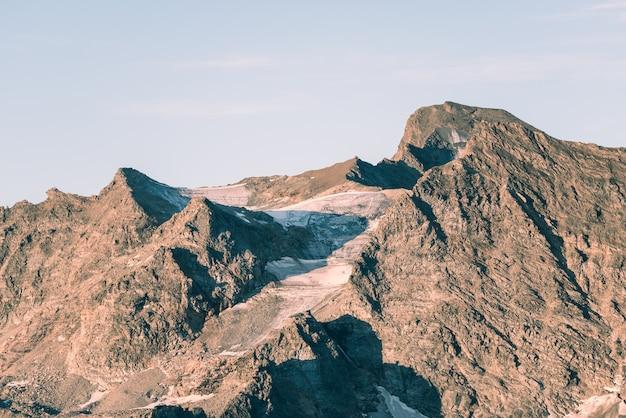 Sonnenunterganglicht über sterbenden gletschern im ruhestand auf den italienischen französischen alpen. klimawandel-konzept. getöntes entsättigtes bild. Premium Fotos