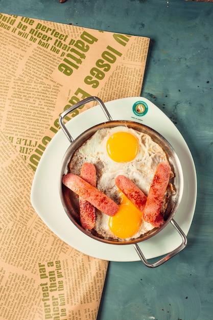 Sonnige eier zum frühstück mit halb geschnittenen und gebratenen würstchen Kostenlose Fotos