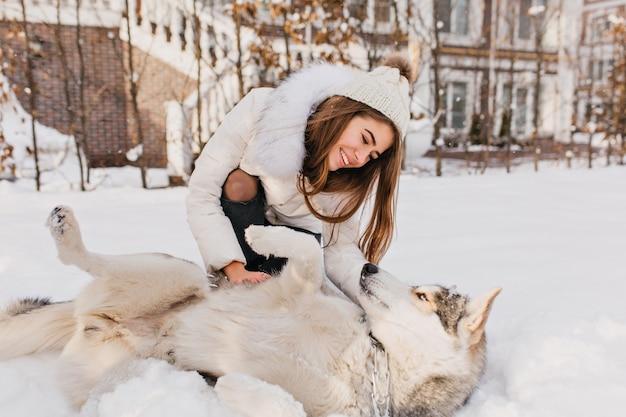 Sonniger gefrorener morgen der modischen genossen jungen frau, die mit husky-hund im schnee im freien spielt. schöne momente, wahre glückliche gefühle, süße haustiere, winterferien. Kostenlose Fotos