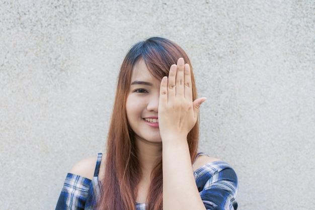 Sonriendo joven hermosa mujer asiática cerrar los ojos con las manos en el fondo de muro de hormigón. vintage efecto de estilo pictures.miling joven hermosa mujer asiática cerrar los ojos con las manos en el fondo de muro de hormigón. vintage efecto estilo imágenes. Kostenlose Fotos