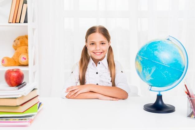 Sorgfältiges schulmädchen, das bei tisch nahe bei kugel im klassenzimmer sitzt Kostenlose Fotos