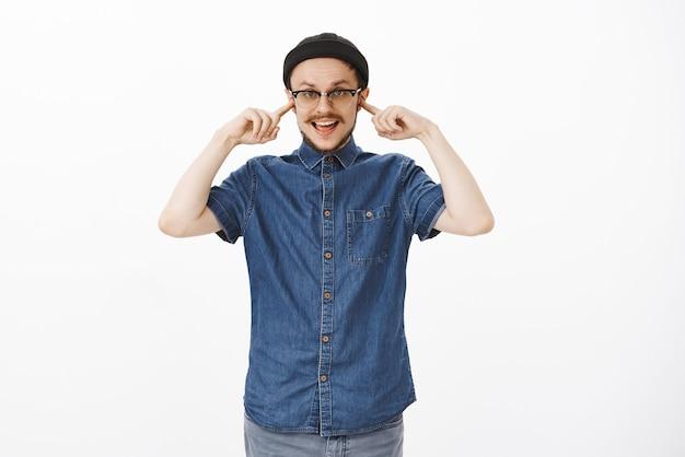 Sorglos gleichgültig gut aussehender stilvoller mann mit schnurrbart in schwarzer mütze und brille, die ohren mit zeigefinger bedeckt, hört nicht zu Kostenlose Fotos
