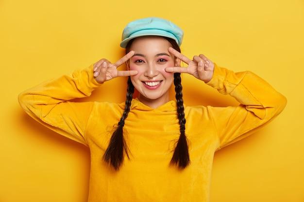 Sorglos lächelnde asiatische dame macht sieg friedensgeste in der nähe der augen, hat fröhliche stimmung, lächelt sanft, trägt lebendiges make-up, trägt stilvollen hut und sweatshirt, isoliert auf gelber wand Kostenlose Fotos