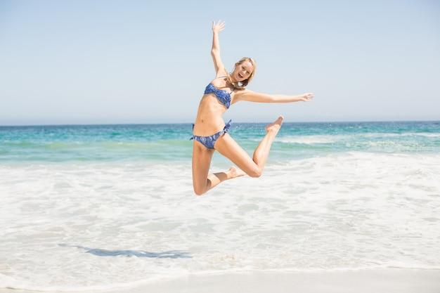 Sorglose frau im bikini, der auf den strand springt Premium Fotos