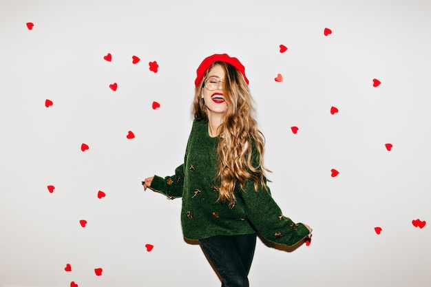 Sorglose frau mit lockigem hellbraunem haar, das am valentinstag mit geschlossenen augen lacht Kostenlose Fotos