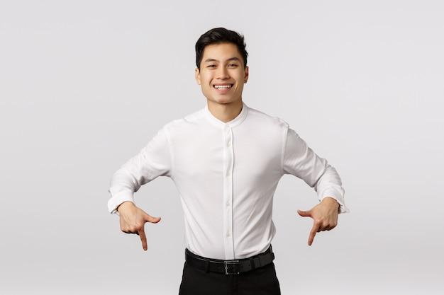 Sorgloser, lächelnder netter und froher asiatischer tausendjähriger kerl in der formellen kleidung, im hemd und in den hosen, unten zeigend Premium Fotos