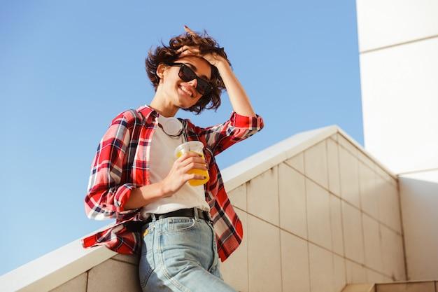 Sorgloses junges mädchen in der sonnenbrille, die orangensaft trinkt Kostenlose Fotos