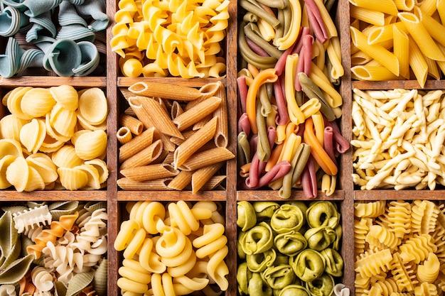 Sortierte bunte italienische teigwaren in der holzkiste Premium Fotos