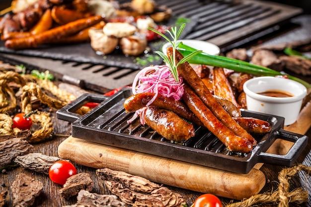 Sortierte gebratene würste auf einem grill auf einem hölzernen brett. Premium Fotos