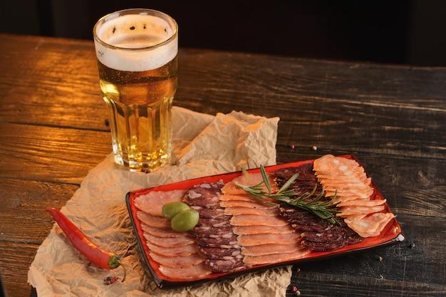 Sortierte geschnittene würste auf einer roten platte. mit einem glas bier. auf einem holztisch Premium Fotos