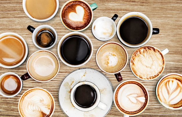 Sortierte kaffeetassen auf einem holztisch Kostenlose Fotos
