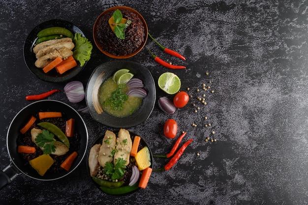 Sortierte nahrung und teller des gemüses, des fleisches und der fische auf einer schwarzen steintabelle. ansicht von oben. Kostenlose Fotos