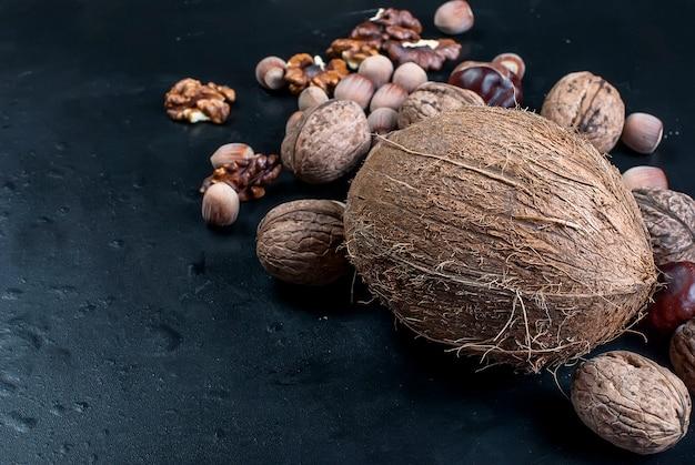 Sortierte nüsse auf einem schwarzen hintergrund Premium Fotos