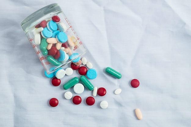 Sortierte pharmazeutische medizinpillen, tabletten und kapseln und flaschenkorn Premium Fotos
