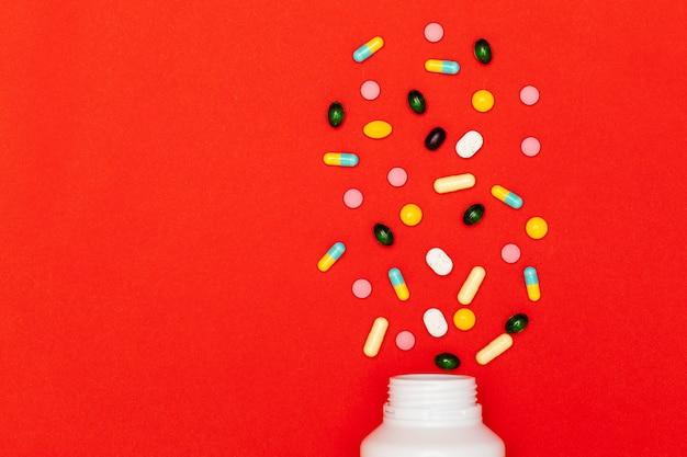 Sortierte verschiedene arten von pillen auf rotem hintergrund Premium Fotos