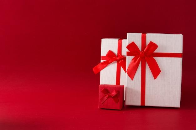 Sortierte weiße geschenkboxen auf rotem hintergrund kopienraum Premium Fotos