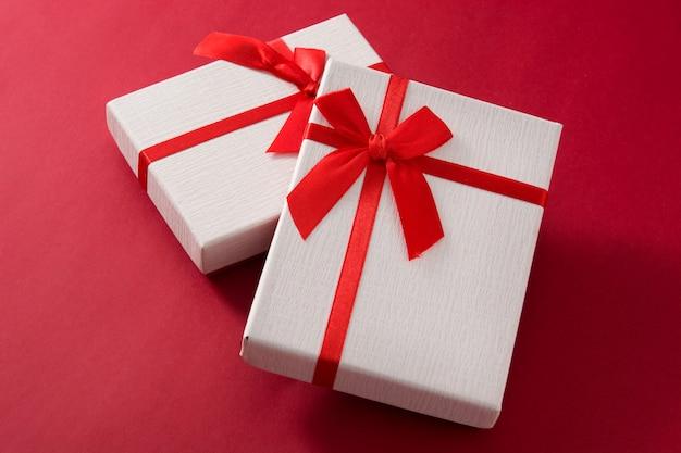 Sortierte weiße geschenkboxen auf rotem hintergrund Premium Fotos