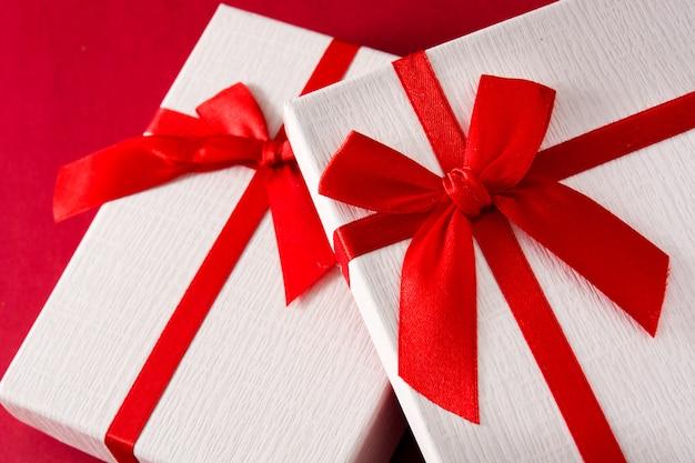 Sortierte weiße geschenkboxen auf rotem hintergrundabschluß oben Premium Fotos
