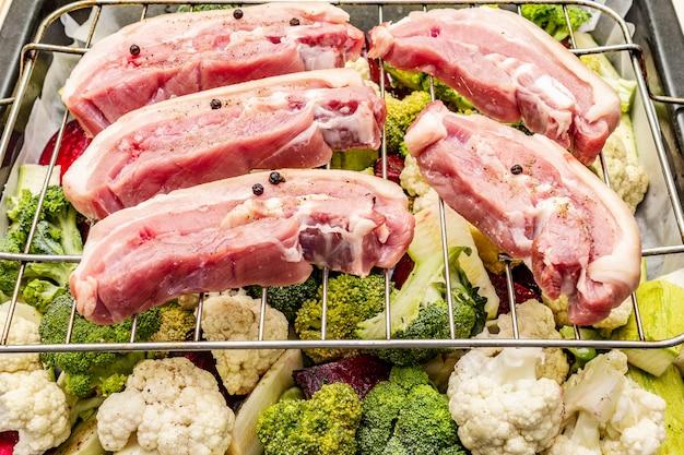 Sortiertes frischgemüse auf einem backblech. rohes schweinebauchfleisch auf dem grill Premium Fotos