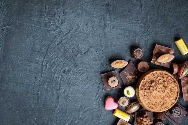 Sortiertes schokoladen- und kakaopulver auf schwarzem Premium Fotos