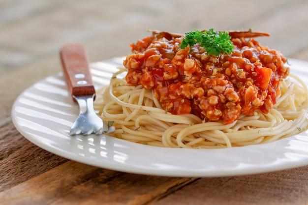Soße des spaghettis bolognese mit rindfleisch oder schweinefleisch, käse, tomaten und gewürzen auf weißer platte Premium Fotos