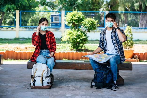Sowohl männliche als auch weibliche touristen sitzen und schauen auf die karte neben der eisenbahn. Kostenlose Fotos