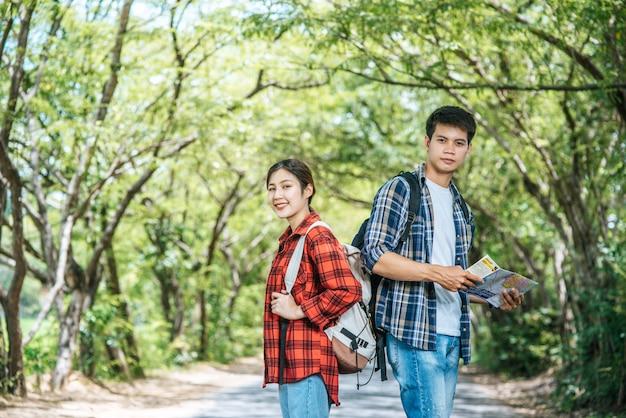 Sowohl männliche als auch weibliche touristen tragen ihre rucksäcke und wenden sich gegeneinander. Kostenlose Fotos