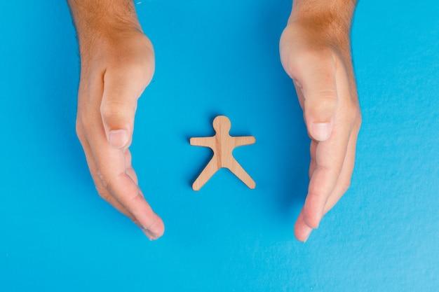 Sozialschutzkonzept auf blauem tisch flach legen. hände, die sich um hölzerne menschliche figur kümmern. Kostenlose Fotos