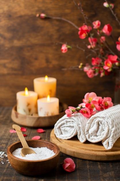 Spa-arrangement mit brennenden kerzen und handtüchern Kostenlose Fotos