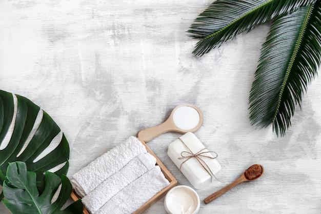 Spa. körperpflegeprodukte auf einem weißen hintergrund mit tropischen blättern. sommeraccessoires. platz für text. Kostenlose Fotos
