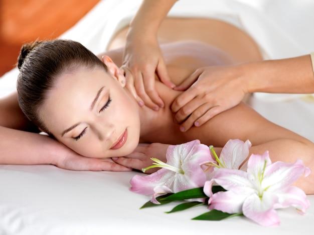 Spa-massage auf einer schulter für junge schöne frau im schönheitssalon Kostenlose Fotos