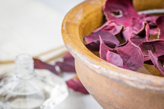 Spa mit schönen rosenblättern und einer tonschale. Premium Fotos