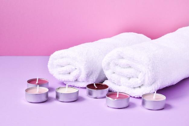 Spa stillleben behandlung mit kerzen und handtüchern auf rosa hintergrund, kopieren platz für text Premium Fotos