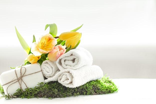 Spa stillleben mit natürlicher seife, handtüchern und gelben tulpen auf einem leicht verschwommenen hintergrund kopieren raum. Kostenlose Fotos