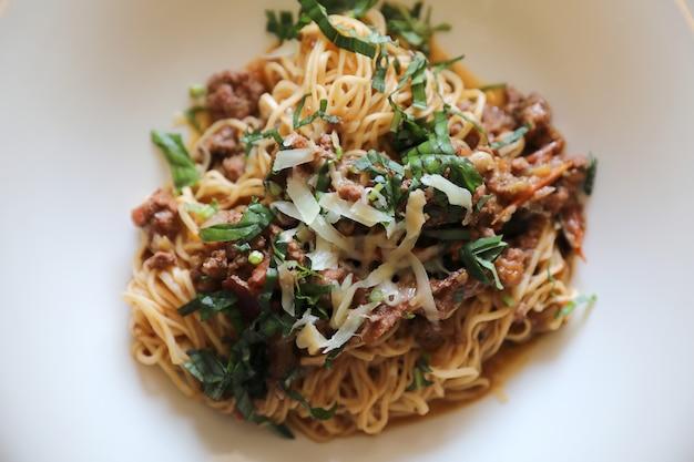 Spaghetti bolognese mit rinderhackfleisch und tomatensauce garniert Premium Fotos
