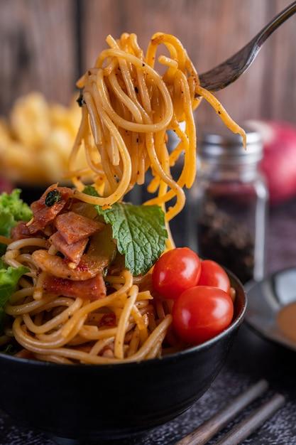 Spaghetti in einer schwarzen tasse mit tomaten und salat. Kostenlose Fotos
