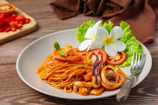 Spaghetti meeresfrüchte mit tomatensauce mit schönen zutaten dekoriert. Kostenlose Fotos