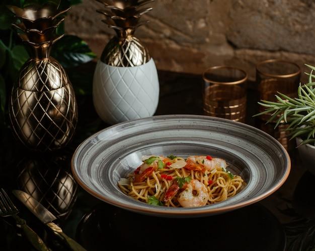 Spaghetti mit meeresfrüchten und frischem gemüse gekocht und in einer grauen granitplatte serviert Kostenlose Fotos