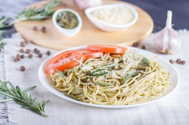 Spaghettinudeln mit pestosoße, tomaten und käse auf einer leinentischdecke Premium Fotos