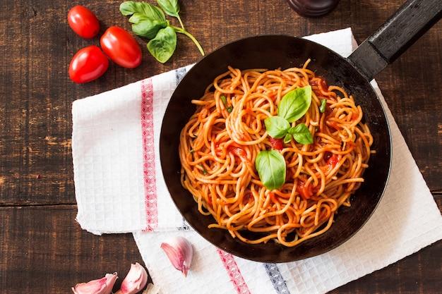 Spaghettis mit basilikumblatt in der bratpfanne auf holztisch mit bestandteilen Kostenlose Fotos