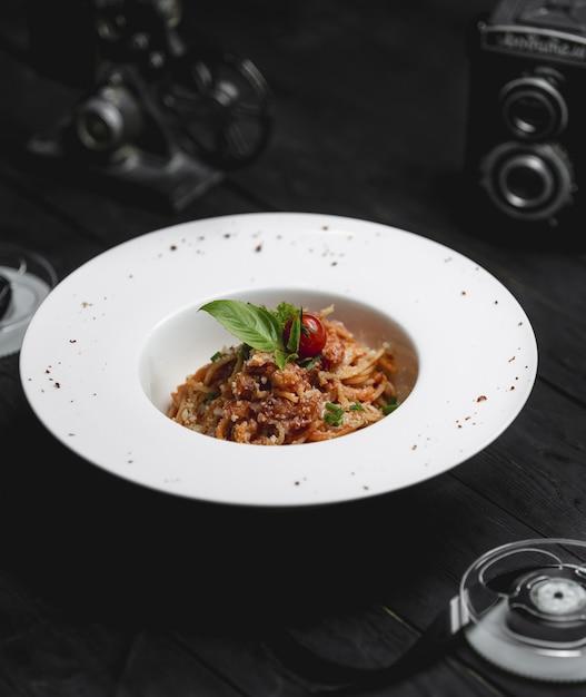 Spaghettiteigwaren in einer weißen schüssel mit kräutern Kostenlose Fotos